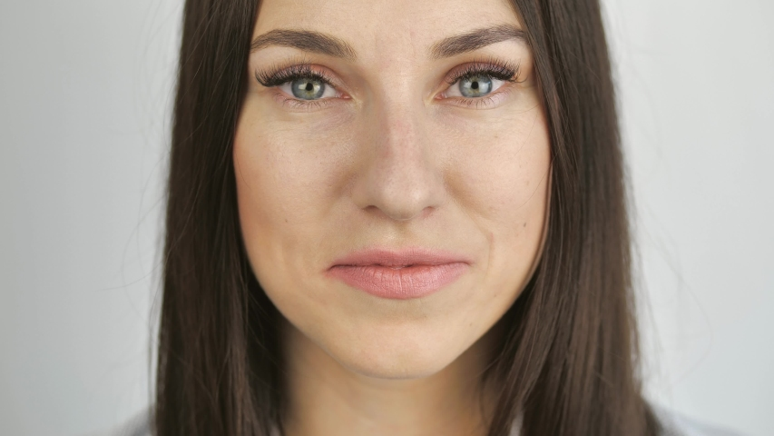 Close up of woman s face, female opening her beautiful blue eyes, Attractive brunette. Natural Beauty make up. Gorgeous woman with long Eyelashes and Attractive Appearance. Slow motion. 4k | Shutterstock HD Video #1054148240