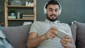 Joyful Arab man is enjoying music through wireless headphones and playing video game in smartphone sitting on sofa in apartment. People and gadgets concept.