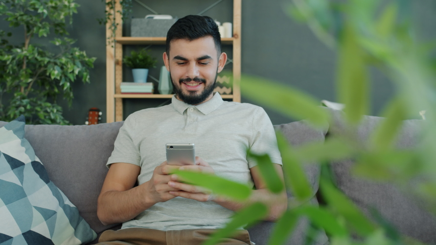 Carefree Arab man in casual clothing is using smartphone texting browsing indoors on couch at home. Modern devices, youth and communication concept.