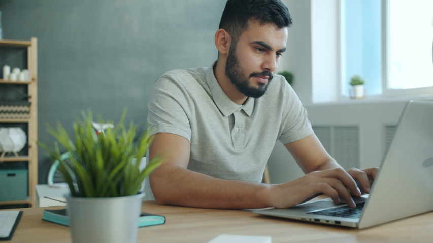 Smiling Arabian man is using laptop texting enjoying friendly communication at home at table. Modern technology, internet and people concept. Royalty-Free Stock Footage #1054148492
