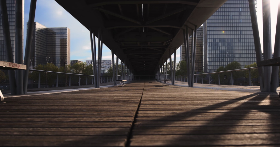 Empty Bercy wood bridge with benches at sunset in Paris with blue sky and François Mitterand library in background, France | Shutterstock HD Video #1054150430