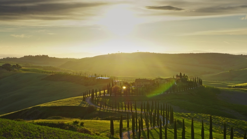 Tuscany landscape with road and cypresses of farmland hill country at sunset. Italy, Europe, zoom out timelapse 4k Royalty-Free Stock Footage #1054159358