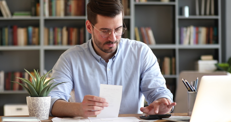 Focused young businessman in glasses holding paper receipt, doing accounting at office. Concentrated bearded man calculating household bills, managing monthly incomes and outcomes alone at home. | Shutterstock HD Video #1054161494