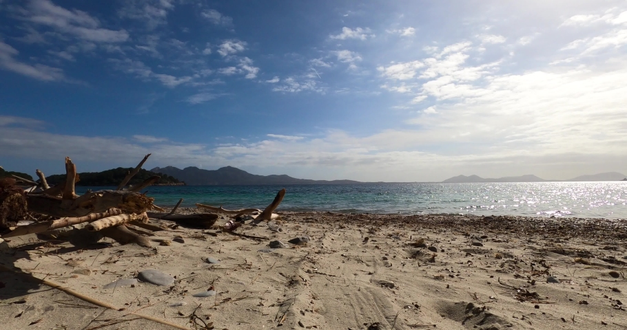 Time lapse of logs on a beach, coast of Majorca, sunny day, in Balearic islands, Spain - Static shot