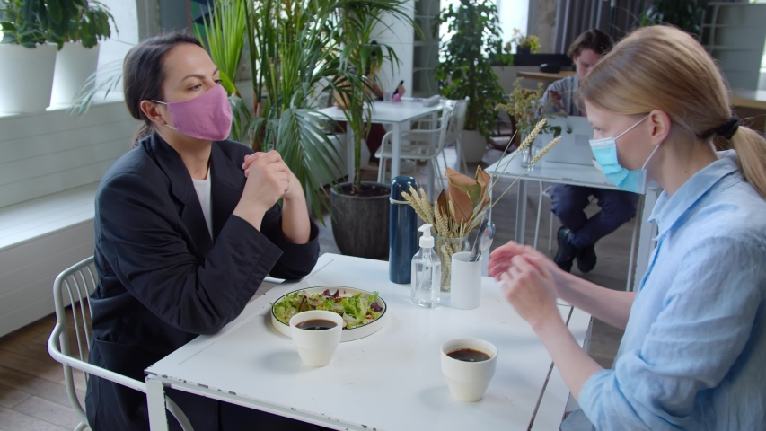 Two girls in a cafe wear protective masks at lunchtime, brunette girl in business black jacket, take off masks and treat hands sanitizer, communicate and smile, drink coffee and eat. Social distance