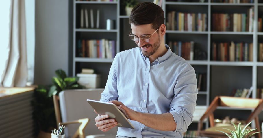Smiling confident young businessman in spectacles standing in office, using corporate software applications on digital tablet. Happy male manager working online on electronic device, managing tasks. Royalty-Free Stock Footage #1054165376