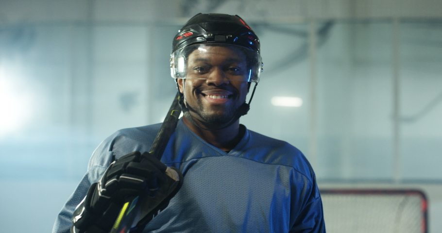 Portrait of happy handsome young African American male hockey player in helmet and with club smiling to camera on ice arena. Close up of cheerful attractive sportsman in casque with stick. | Shutterstock HD Video #1054165481
