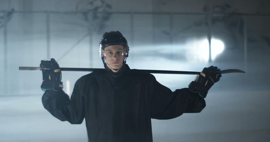 Portrait shot on young Caucasian handsome male hockey player in helmet looking at camera and holding club over shoulders on icy arena. Sportsman in casque with stick. | Shutterstock HD Video #1054165484