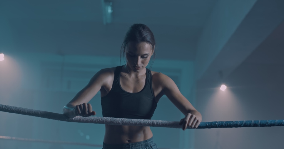 Caucasian female beautiful boxer leaning on ring rope and feeling herself tired and bad. Attractive sportswoman having pain in muscles. Body ache after sport training.