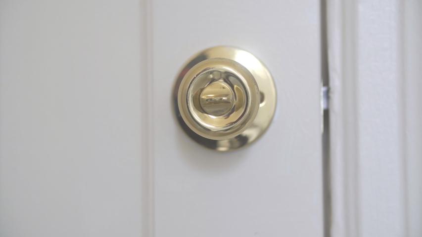 Close-up of doorknob. Hand opening and closing door or locking and unlocking gold door handle.  | Shutterstock HD Video #1054166297