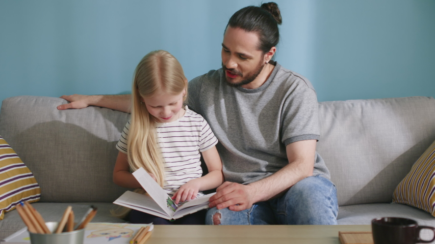 Small beautiful girl is spending time with her daddy, studying together, reading an interesting story and discussing some details, happy childhood, Slow motion.