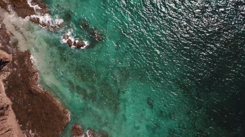 Steady Drone Overhead of Exotic Beach with Cristal Clear Water, Waves, and Ocean Reflections. UHD 4K. Sea in Costa Rica. | Shutterstock HD Video #1054169489