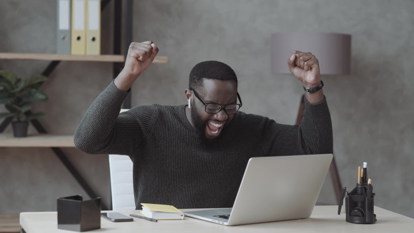 Overjoyed black male student sit at desk look at laptop screen scream passing exam getting high grade, excited african American guy feel euphoric receiving pleasant email message on computer