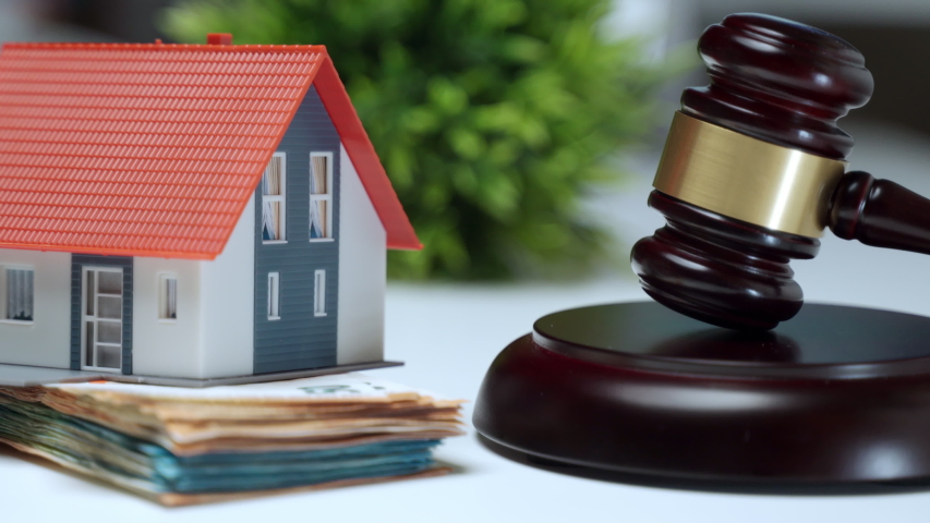 Miniature plastic house staying on stack of money near the wooden judge gavel, property auction concept. Financial transactions, investment and expenses during buying or selling house process | Shutterstock HD Video #1054171010