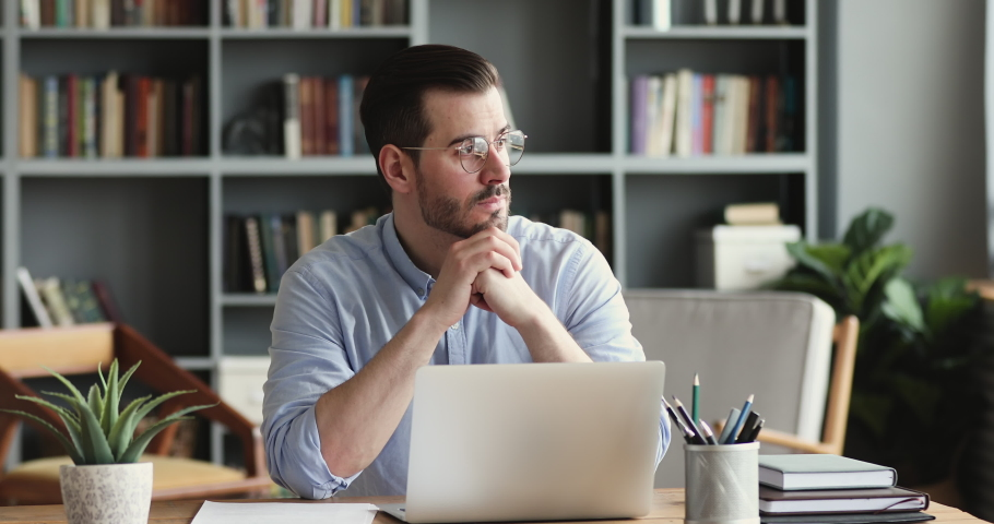 Thoughtful young businessman looking away, considering risks. Focused software developer programmer finding problem solution, writing code on computer. Concentrated manager analyzing market online. | Shutterstock HD Video #1054174040
