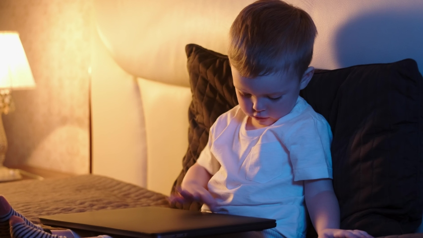 Cute caucasian boy in bedroom late at night sitting on bed opening laptop, typing something interesting surfing Internet. night light in room, moonlight shines from window. Dolly slides through video. | Shutterstock HD Video #1054174208