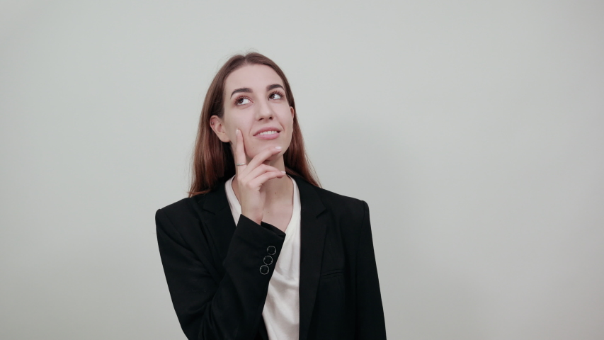 Hand on chin thinking about question, pensive expression. Doubt. Thoughtful face. Using that incredibly sharp business mind. Young attractive woman with brown hair in a light t-shirt, black jacket