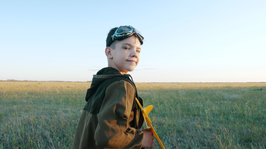 Smiling Child Boy Looking at Camera Plays Funny Game Walking on Field, Launches Toy Airplane to Fly Outdoor at Sunset. Profession Interest, Imagination Freedom, Active Childhood of Little Future Pilot
