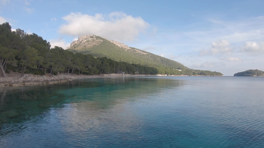 Panoramic view of Majorca (Mallorca) island, Baleares, Spain. Beautiful panorama of coastline, white sand beach with pine trees, mountains, crystal clear water. Beach de Formentor with no people.