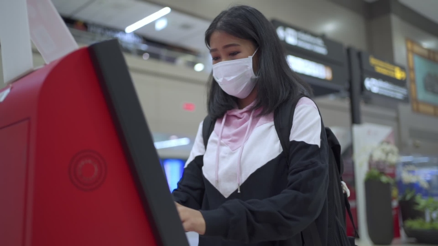 Asain woman passenger wear white mask doing self check-in at airport terminal, e-ticket booking, woman using ticket kiosk machine, covid-19 pandemic, new normal social distance, slow motion