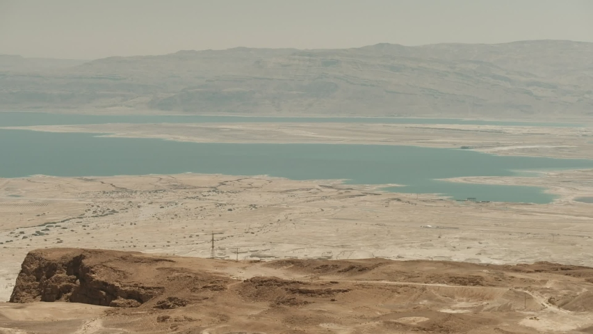 The Masada fortress: an ancient fortification in the Southern District of Israel situated on top of an isolated rock plateau right above the Dead Sea. camera pan from Dead sea to the fortress.