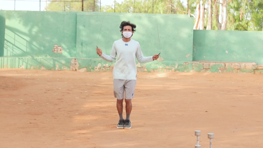 Young man with medical face mask skipping exercises at outdoors - Concept of outdoor, fitness, workout during coronavirus or covid-19 outbreak.