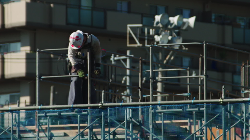 Construction worker on a building site in Japan. He is working with a spanner on scaffolding and is wearing a hard hat Royalty-Free Stock Footage #1054194809