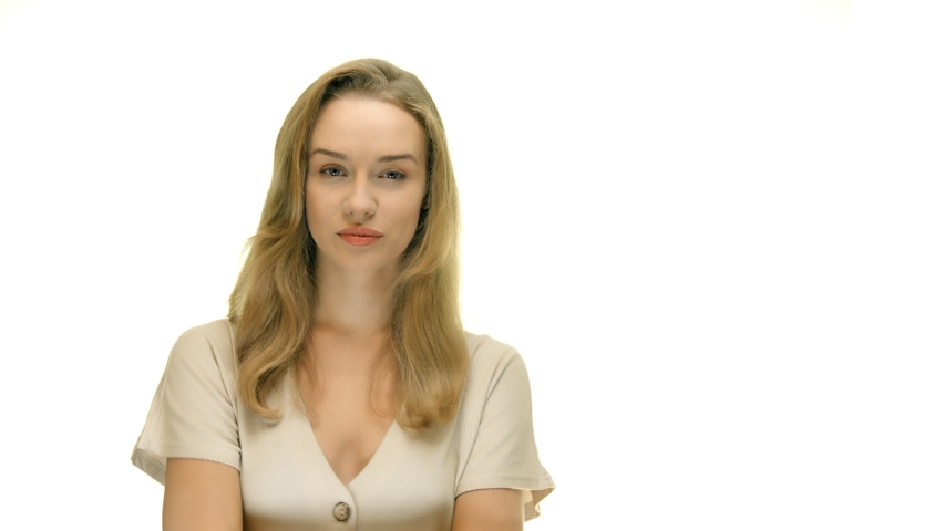The young woman puts a finger to her lips. Hides a secret. A woman is standing against a white background. Movie for advertising with copy space.   Shutterstock HD Video #1054199639