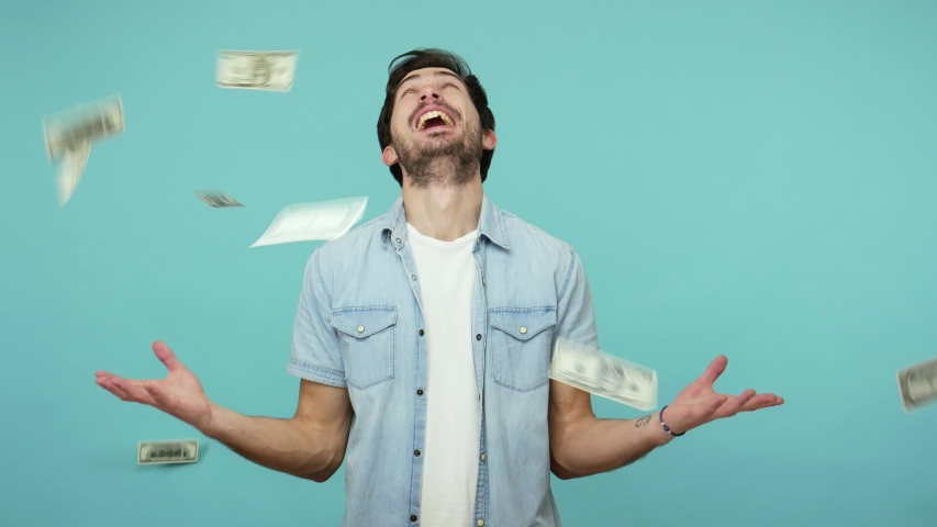 Excited happy lottery winner, glad bearded guy in jeans shirt looking up and shouting from happiness while money rain falling from above, rich man enjoying wealth. indoor studio shot, blue background