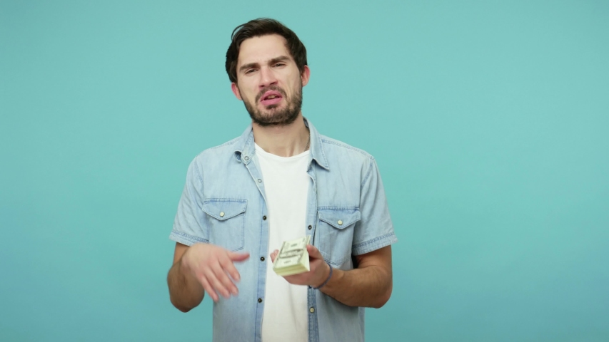 Handsome bearded guy in jeans shirt scattering dollars with arrogant haughty expression, throwing around cash, squandering, wasting money carelessly. indoor studio shot isolated on blue background   Shutterstock HD Video #1054200608