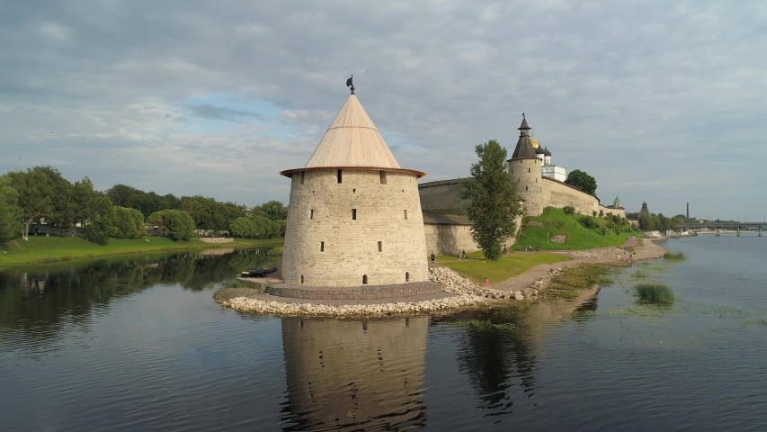 Aerial climb Pskov fortress stronghold stone wall tower. Fortification medieval Kremlin surrounded by moat by river. Russia real authentic landmark. Trinity Cathedral. Summer sunny dramatic clouds. 4k