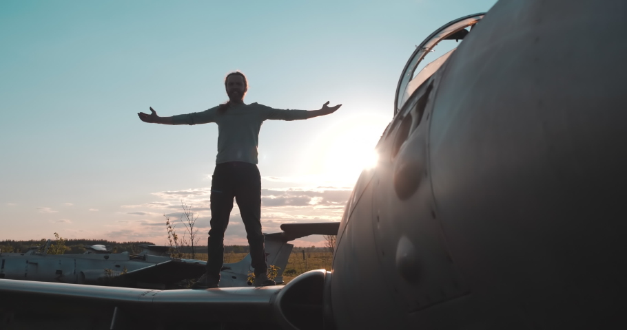 Front close-up view of smiling active bearded man standing on the wing of abandoned combat aircraft from Second World War with arms spread out against backdrop of bright sun and glare. Old airfield.