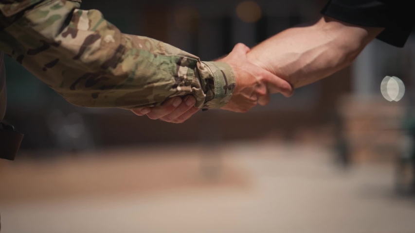Military man and civilian grabbing arms shaking hands close up slow motion