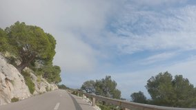 Point of view footage of driving by road through beautiful rocky mountain landscape with pine trees. 4K slow motion video during cloudy day. Mallorca island, Spain. Travel by countryside