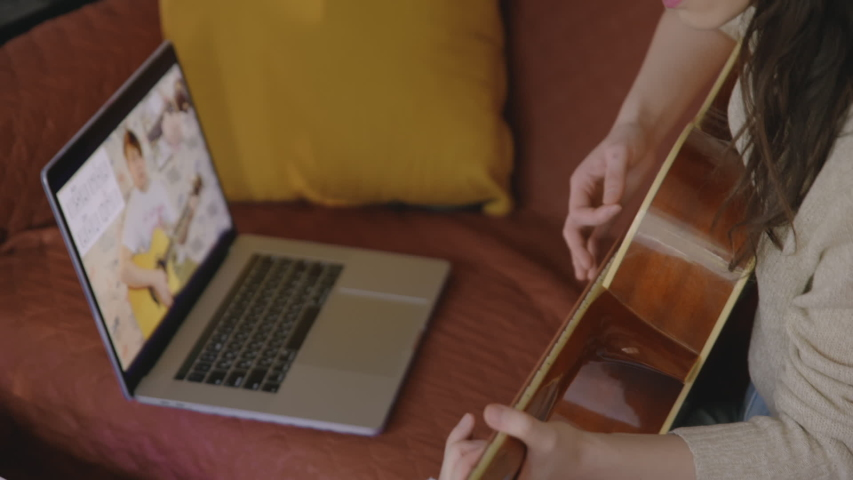 Stay home, solo activity Pretty girl watching online lesson and practising music. Young asian woman playing guitar at home. Aspiring musician learning to play musical instrument using laptop. | Shutterstock HD Video #1054212704
