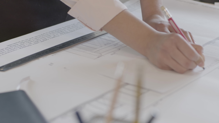 A young female architect draws a building plan, measures the dimensions of the blueprint with a ruler and a pencil on the desktop in the design office. Translating text in a drawing: Side view | Shutterstock HD Video #1054213586
