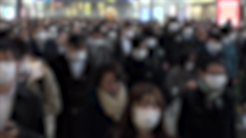 TOKYO, JAPAN - MARCH 2020 : Crowd of people walking at Shinagawa station in morning rush hour. Many commuters going to work. People wearing mask to protect from Coronavirus (COVID-19). Blurred shot.