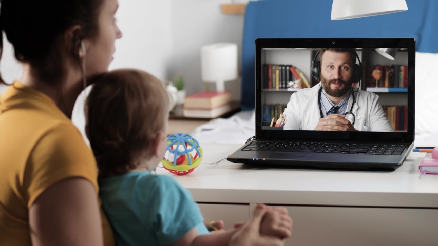 Doctor online consultation video link. Woman in headphones with child on her knees in bedroom looks at laptop screen and talks to man in white coat over Internet video link. Close-up Royalty-Free Stock Footage #1054215107