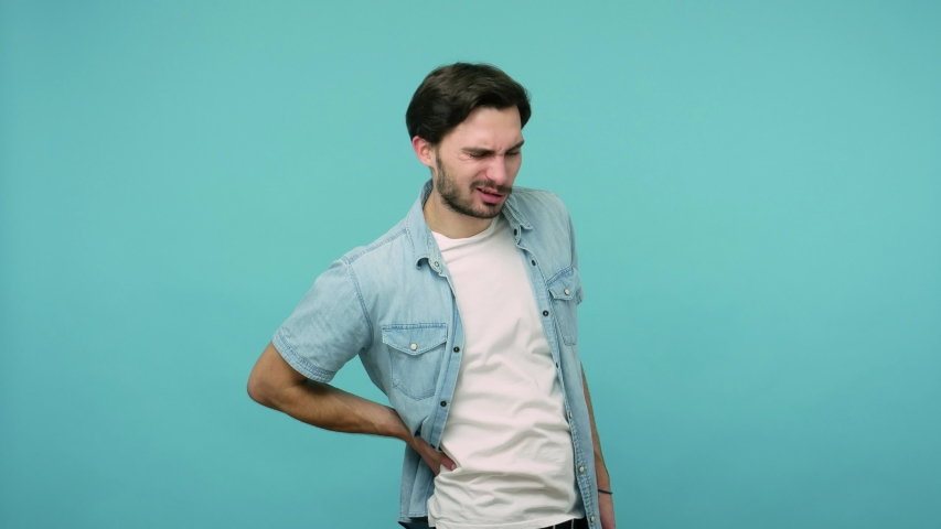 Backache. Tired unhealthy male worker in jeans shirt touching injured sore back, suffering lower lumbar discomfort, muscle pain of overwork, pinched nerve. studio shot isolated on blue background | Shutterstock HD Video #1054232105