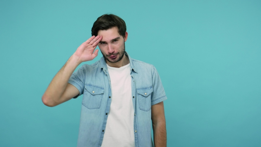 Positive bearded guy in jeans shirt saluting with hand, saying yes sir and looking at camera with humorous mockery expression, pretending to listen order. studio shot isolated on blue background | Shutterstock HD Video #1054232165