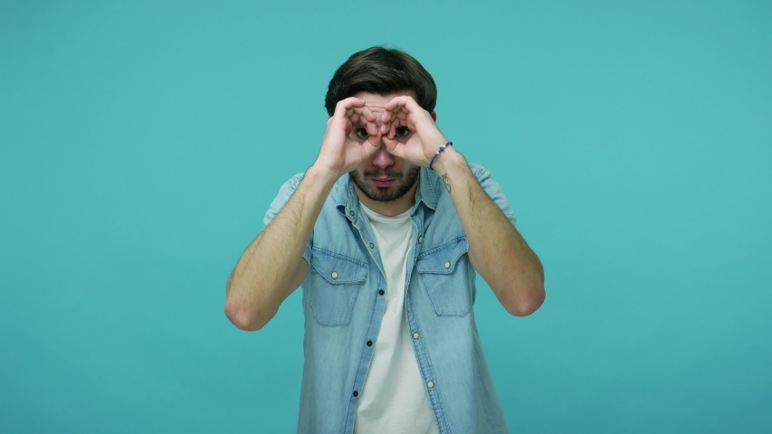 Nosy curious guy in jeans shirt looking through binocular gesture, seeking something in distance, watching far away with amazement and shock, exploring way. studio shot isolated on blue background