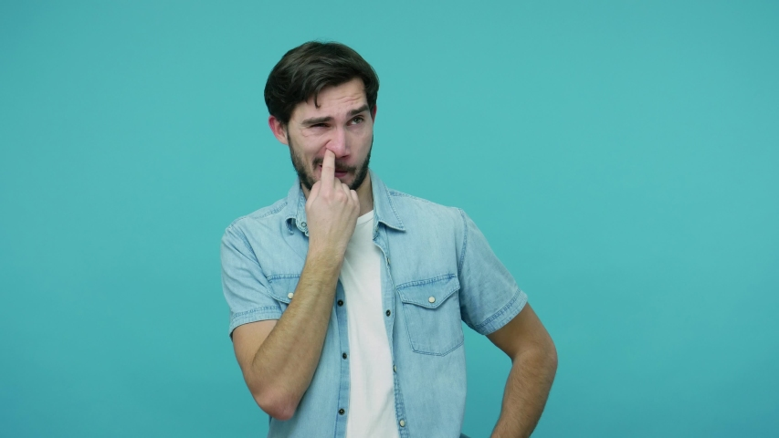 Comical bearded guy in jeans shirt picking dirty nose, pulling out boogers with stupid humorous expression, uncultured bad habit, misconduct concept. indoor studio shot isolated on blue background