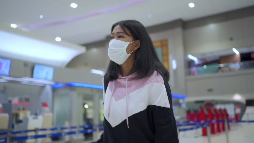 Young tan skin Asian woman in protective medical mask walking in queue line at airport terminal departure hall, traveling leaving home, covid-19 pandemic, new normal social distance, slow motion