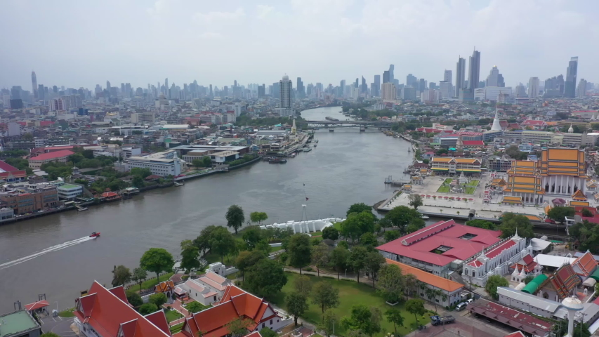 Aerial video of Wat Arun and Bangkok city skyline. Wat Arun is the old temple located near Chaophraya river in Bangkok of Thailand. | Shutterstock HD Video #1054252241