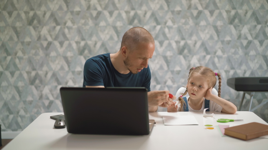 Concept of distance learning of father and little student daughter at white table in room of house, with laptop, scissors, book, dad shows how to correctly paste colored red circle | Shutterstock HD Video #1054252592