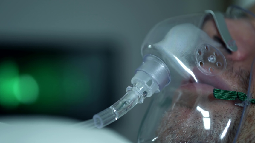 Male Patient Breathing Oxygen Support In Hospital, Next To Heart Rate Machine. Royalty-Free Stock Footage #1054258874