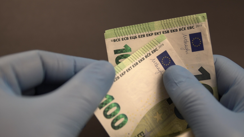 Money exchange during Covid-19 times: Hands with blue protective medical gloves are counting European 100 (hundred) EURO money banknotes and leave them on black background. | Shutterstock HD Video #1054259678