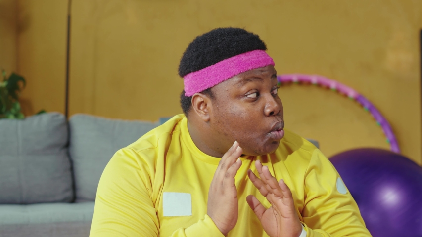 Cunning fat african american man practicing yoga meditation with personal trainer and secretly eating a cookie. Funny scene. Fitness parody. Humor concept. | Shutterstock HD Video #1054267412