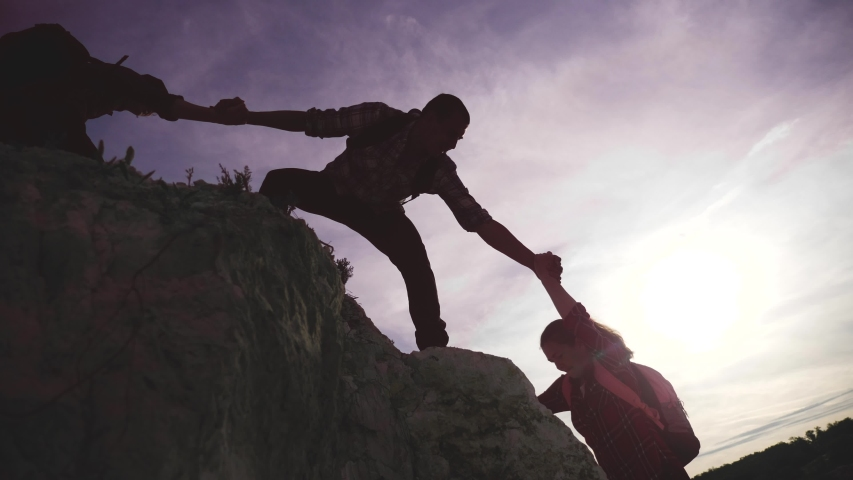 Teamwork help business travel silhouette concept lifestyle . group team of tourists lends a helping hand climb the cliffs mountains. teamwork people climbers climb to the top overcoming helping hand | Shutterstock HD Video #1054272230