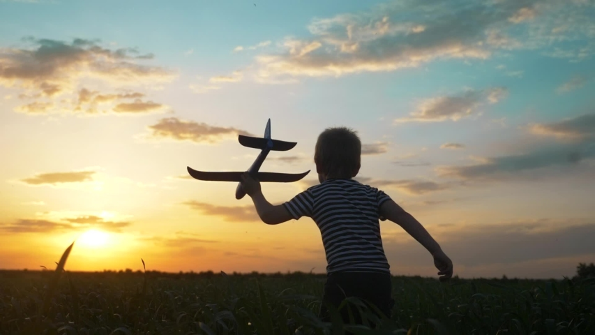 Happy boy child run with an airplane. kid silhouette play plane. happy family dream freedom airplane concept. lifestyle son kid run on wheat field at sunset holds in his hands dream toy aircraft